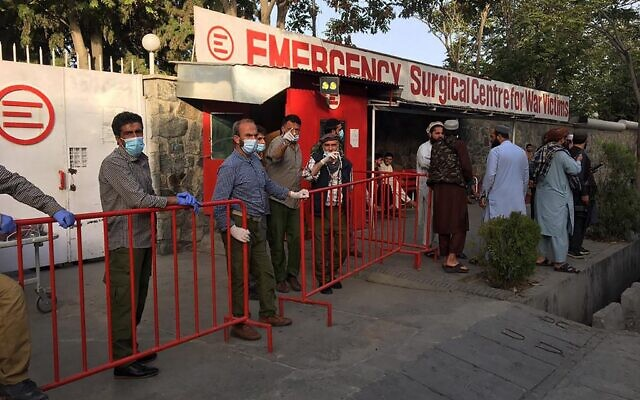 Afghan medical staff members stand at the entrance of a hospital as they wait to receive the victims of an explosion in Kabul on October 3, 2021. (Hoshang HASHIMI / AFP)