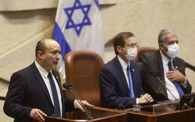 Prime Minister Naftali Bennett stands next to President Isaac Herzog as he addresses the Knesset in Jerusalem on October 4, 2021. (Menahem KAHANA / AFP)