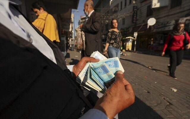A Palestinian man counts a stack of Israeli Shekels in the West Bank city of Ramallah on October 5, 2021. (ABBAS MOMANI / AFP)