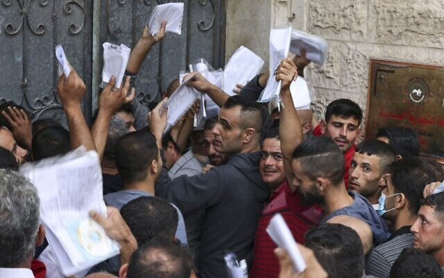 Palestinian men gather to apply for work permits in Israel, at Jabalia refugee camp in the northern Gaza Strip, on October 6, 2021. (MAHMUD HAMS / AFP)
