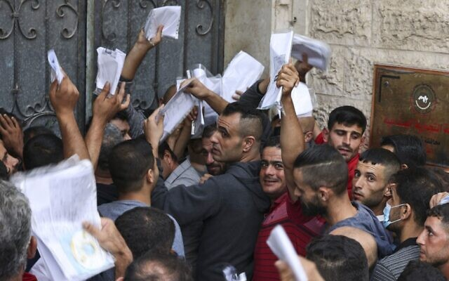 Palestinian men gather to apply for work permits in Israel, at Jabaliya refugee camp in the northern Gaza Strip, on October 6, 2021. (Mahmud Hams/AFP)