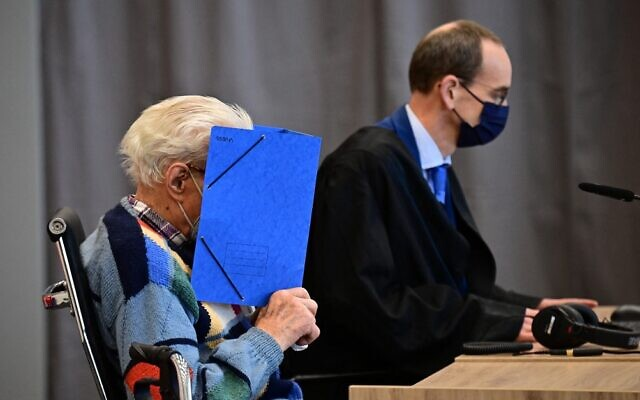 Defendant Josef S (L) sits next to his lawyer Stefan Waterkamp and hides his face behind a folder as he waits for the start of his trial in Brandenburg an der Havel, northeastern Germany, on October 7, 2021. (Tobias Schwarz / AFP)