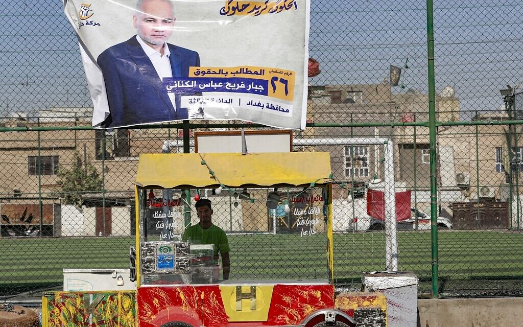 An Iraqi street vendor stands beneath an electoral billboard of a candidate for the upcoming parliamentary elections, in the capital Baghdad's Sadr City neighborhood, on October 9, 2021. (AHMAD AL-RUBAYE / AFP)