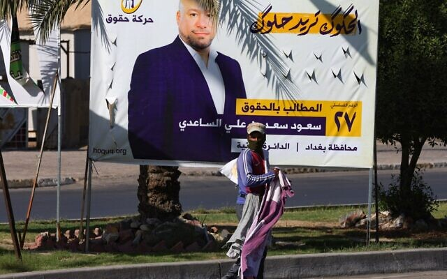 A street vendor stands in front of an electoral billboard of a candidate for the upcoming parliamentary elections, in the capital Baghdad's Sadr City neighbourhood, on October 9, 2021 (AHMAD AL-RUBAYE / AFP)