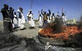 Members of the Beja ethnic group of eastern Sudan gather around burning tires as they demonstrate outside the Osman Digna port in Sudan's northeastern Red Sea coastal city of Suakin on October 9, 2021 (ASHRAF SHAZLY / AFP)