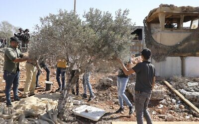 Illustrative: An Israeli soldier (Top-R) looks on as Palestinian and foreign volunteers and activists pick olives next to the outpost of Evyatar in in the West Bank, on October 10, 2021. (JAAFAR ASHTIYEH / AFP)