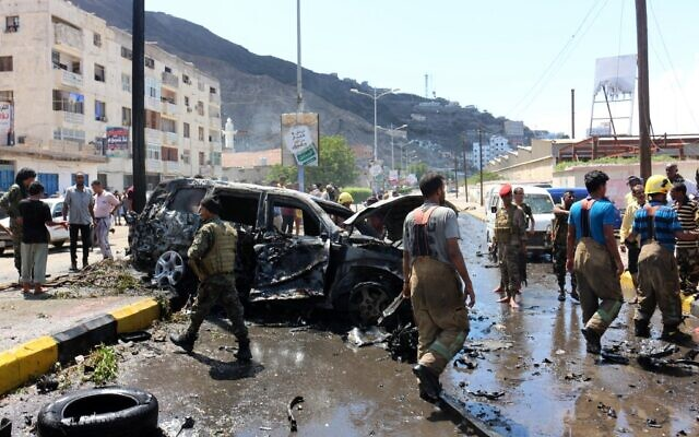 Yemeni security forces and rescue teams gather around the skeleton of a burnt car following an explosion that hit Yemen's southern port city of Aden, on October 10, 2021. (Saleh Al-OBEIDI / AFP)
