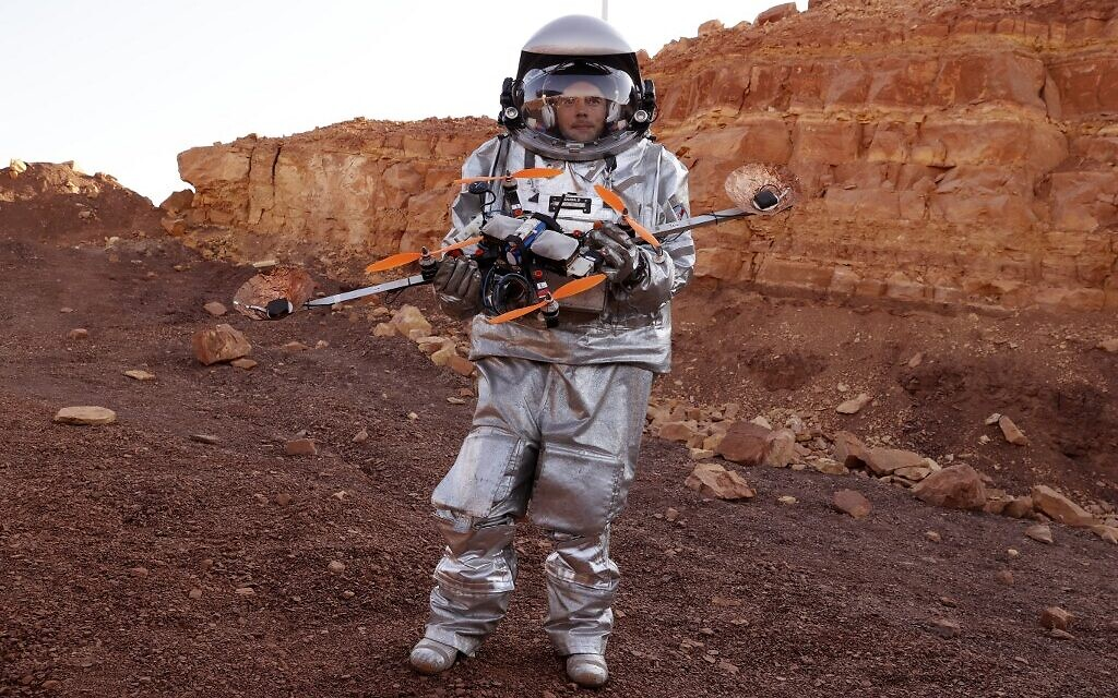 An astronaut from a team from Europe and Israel and dressed in a spacesuit holds a quadcopter drone during a training mission for planet Mars at a site that simulates an off-site station at the Ramon Crater in Mitzpe Ramon in Israel's southern Negev desert on October 10, 2021. (Photo by JACK GUEZ / AFP)