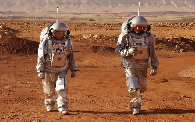 A couple of astronauts from a team from Europe and Israel walk in spacesuits during a training mission for planet Mars at a site that simulates an off-site station at the Ramon Crater in Mitzpe Ramon in Israel's southern Negev desert on October 10, 2021. (Photo by JACK GUEZ / AFP)