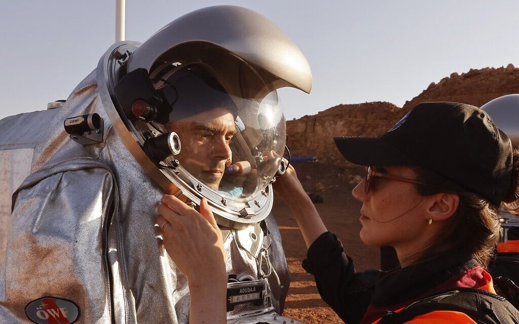 Technicians assist an astronaut from a team from Europe and Israel to suit up in a spacesuit before starting a training mission for planet Mars at a site that simulates an off-site station at the Ramon Crater in Mitzpe Ramon in Israel's southern Negev desert on October 10, 2021. (Photo by JACK GUEZ / AFP)