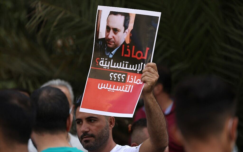 A supporter of Hezbollah and the Amal movement carries a portrait of Judge Tarek Bitar, the Beirut blast lead investigator, near the Justice Palace in the capital Beirut on October 14, 2021, during a gathering to demand his dismissal. (JOSEPH EID / AFP)