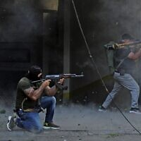 Shiite fighters from Hezbollah and Amal terror movements take aim with (L to R) a Kalashnikov assault rifle and a rocket-propelled grenade launcher amidst clashes in the area of Tayouneh, in the southern suburb of the capital Beirut, on October 14, 2021 (IBRAHIM AMRO / AFP)