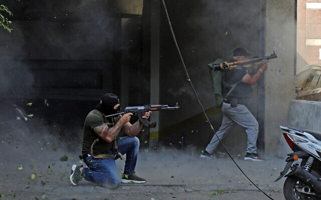 Shiite fighters from Hezbollah and Amal movements take aim with (L to R) a Kalashnikov assault rifle and a rocket-propelled grenade launcher amidst clashes in the area of Tayouneh, in the southern suburb of the capital Beirut, on October 14, 2021. (Ibrahim Amro/AFP)