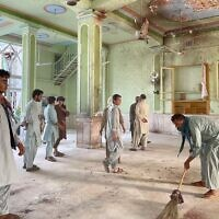 Afghan men inspect damage inside a Shiite mosque in Kandahar on October 15, 2021, after a suicide bomb attack during Friday prayers. (JAVED TANVEER / AFP)