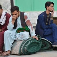 Afghan men sit in a courtyard inside a Shiite mosque in Kandahar on October 15, 2021, after a suicide bomb attack during Friday prayers (Javed TANVEER / AFP)
