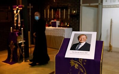 A photograph of Conservative British lawmaker David Amess, who was fatally stabbed, is pictured prior to a service at Saint Peter's Catholic Parish of Eastwood in Leigh-on-Sea in southeast England on October 15, 2021 (Tolga Akmen / AFP)