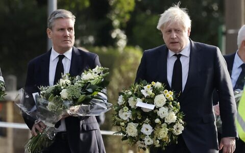 Britain's Prime Minister Boris Johnson (right) and Britain's main opposition Labour Party leader Keir Starmer carry floral tributes as they arrive at the scene of the fatal stabbing of Conservative British lawmaker David Amess, at Belfairs Methodist Church in Leigh-on-Sea, a district of Southend-on-Sea, in southeast England, on October 16, 2021 (Tolga Akmen/AFP)