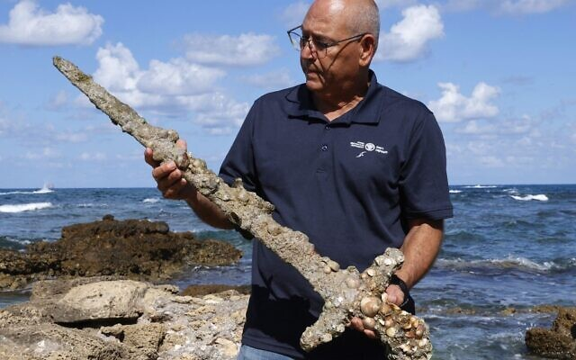 Jacob Sharvit of the Israel Antiquities Authority displays an ancient one-meter-long sword that experts say dates back to the Crusader-era and is believed to have belonged to a Crusader, at the beach in Caesarea, on October 19, 2021 days after being discovered by a local diver. (JACK GUEZ / AFP)