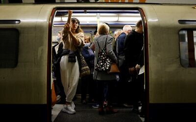 Commuters, some wearing face masks to help prevent the spread of coronavirus, wait for an underground train to leave from a station in central London, on October 19, 2021. (Tolga Akmen/AFP)