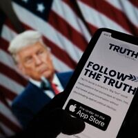 """This illustration photo shows a person checking the app store on a smartphone for """"Truth Social"""", with a photo of former US president Donald Trump on a computer screen in the background, in Los Angeles, October 20, 2021. (Chris DELMAS / AFP)"""