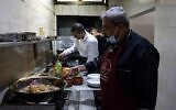 Moin (R) and Mustapha Abu Hassira work in the kitchen of Roma fish restaurant owned by the Abu Hassira family in Gaza City, on October 23, 2021. (MOHAMMED ABED / AFP)