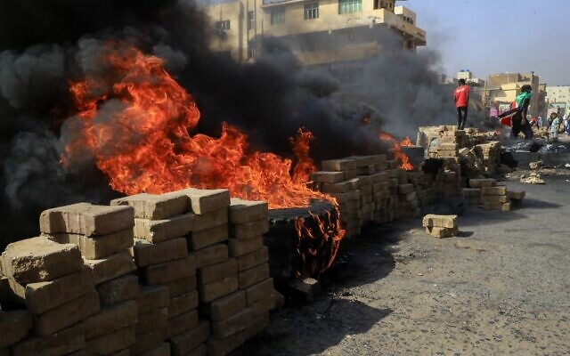 Sudanese protesters burn tires to block a road in Khartoum on October 25, 2021 (Ashraf SHAZLY / AFP)