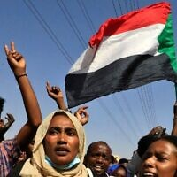 Sudanese protesters flash victory signs and lift national flags as they demonstrate on 60th Street in the capital Khartoum, to denounce overnight detentions by the army of government members, on October 25, 2021. (Photo by AFP)