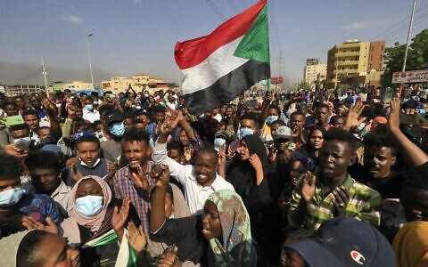 Sudanese protesters lift national flags as they rally in the capital Khartoum, to denounce overnight detentions by the army of government members, on October 25, 2021 (Photo by AFP)