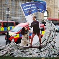 A demonstrator poses with an installation depicting Facebook founder Mark Zuckerberg surfing on a wave of cash and surrounded by distressed teenagers, during a protest opposite the Houses of Parliament in central London as Facebook whistleblower Frances Haugen was set to testify to British lawmakers, on October 25, 2021. (Tolga Akmen / AFP)