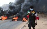 A Sudanese protester draped with the national flag flashes the victory sign next to burning tires, during a demonstration in the capital Khartoum to denounce overnight detentions by the military of members of Sudan's government, on October 25, 2021. (AFP)