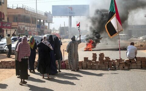 Sudanese protesters lift national flags next to a brick roadblock during a demonstration in the capital Khartoum, on October 25, 2021, to denounce overnight detentions by the army of members of Sudan's government. (Photo by AFP)