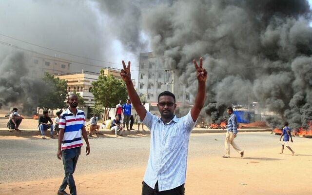 A Sudanese demonstrator flashes the victory sign during a demonstration in the capital Khartoum, on October 25, 2021 (AFP)