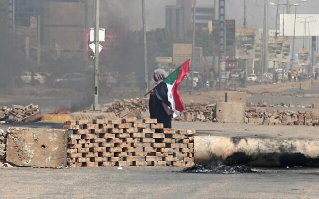 A Sudanese demonstrator carrying a national flag walks by roadblocks set up by protesters on a street in the capital Khartoum, on October 26, 2021. (AFP)