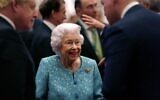 Britain's Queen Elizabeth II (center) and Britain's Prime Minister Boris Johnson (left) greet guests during a reception to mark the Global Investment Summit, at Windsor Castle in Windsor, west of London, on October 19, 2021. (Alastair Grant/Pool/AFP)