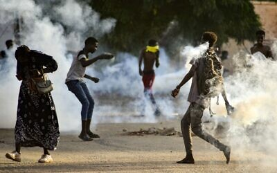 Sudanese youths confront security forces amidst tear gas fired by them to disperse protesters in the capital Khartoum, on October 27, 2021, amid ongoing demonstrations against a military takeover that has sparked widespread international condemnation. (AFP)