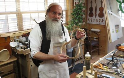 Zev Zalman Ludwick, once a denizen of the heavy metal music scene, poses in his luthier studio in Silver Spring, Maryland on May 23, 2021. (Ron Kampeas/ JTA)