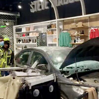 A car that crashed into a clothing store at a strip mall in the northern city of Kiryat Ata, October 23, 2021. (Screen capture: Twitter)