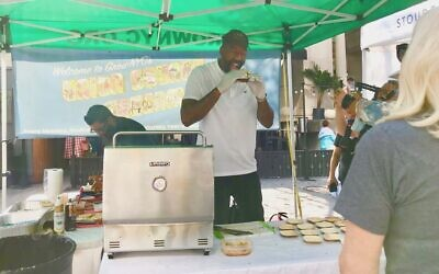 Amar'e Stoudemire, assistant coach of the Brooklyn Nets, samples one of his own signature Stoudemire Farms burgers at his booth at the Union Square Greenmarket in Manhattan, October 15, 2021. (Julia Gergely via JTA)