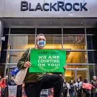A demonstrator kneels in front of the headquarters of BlackRock in Manhattan, demanding the investment firm's CEO Larry Fink defund the fossil fuel industry, October 18, 2021. (courtesy, Erik McGregor via JTA)