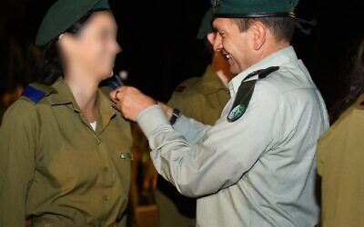 Military Intelligence chief Aharon Haliva, right, presents ranks to a new intelligence officer during a ceremony on October 13, 2021. (Israel Defense Forces)
