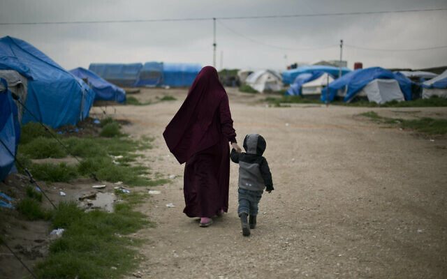 A foreign national married to an Islamic State member walks with their son at Camp Roj in north Syria, March 27, 2019. (Maya Alleruzzo/AP)