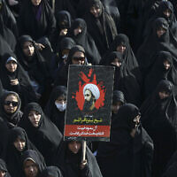 An Iranian woman holds up a poster showing Sheikh Nimr al-Nimr, a prominent opposition Saudi Shiite cleric who was executed by Saudi Arabia, in Tehran, Iran, during a protest on January 4, 2016. (AP Photo/Vahid Salemi)