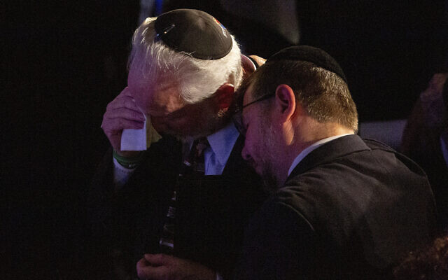 Rabbi Jeffrey Myers, center, of the Tree of Life/Or L'Simcha Congregation, is comforted after saying a prayer for the souls of the deceased during the one-year commemoration of the Tree of Life synagogue attack, at Soldiers & Sailors Memorial Hall and Museum,  October 27, 2019, in Pittsburgh. (AP Photo/Rebecca Droke)