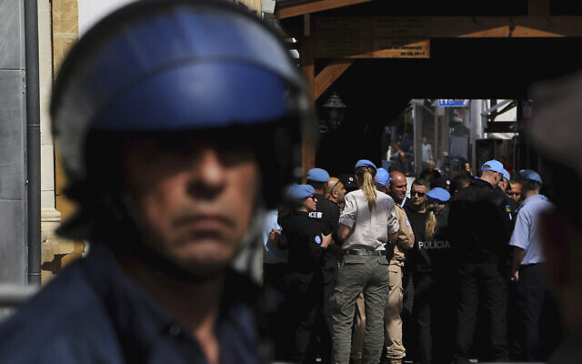A Greek police officer, foreground, stands guard as UN peacekeepers block the  closed crossing point in the divided capital of Nicosia, Cyprus, March 9, 2020.  (AP Photo/Petros Karadjias)