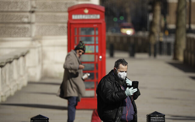 Illustrative: A man wearing a mask looks at his phone near Parliament Square, in London, March 25, 2020. (AP Photo/Matt Dunham)