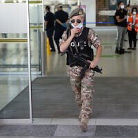 Illustrative: A female police officer adjust her mask as she guards at Cyprus' main airport in Larnaca, on June 9, 2020. (AP Photo/Petros Karadjias)
