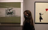 A member of staff from Bonhams auction house stands between two works by British artist Banksy: 'Girl with Balloon 2004', right, and 'Heavy Weapon' 2000, in London, Thursday, Oct. 1, 2020. (Alastair Grant/AP)