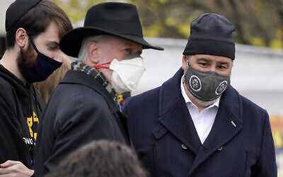 Rabbi Jeffrey Myers, center, his son Aaron, left, and Pittsburgh Mayor Bill Peduto gather outside the Tree of Life synagogue in Pittsburgh for a moment of silence on October 27, 2020, the second anniversary of the shooting at the synagogue, that killed 11 worshipers. (AP Photo/Gene J. Puskar)