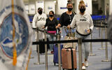 International passengers arrive at Miami international Airport before they are screened by US Customs and Border Protection (CBP) using facial biometrics to automate manual document checks required for admission into the US on Friday, Nov. 20, 2020, in Miami. (AP Photo/Lynne Sladky)