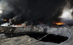 In this Oct. 4, 2016 file photo, oil fields in the town of Qayyarah burn, nearly a month after fleeing Islamic State militants set fire to the oil. (AP/Bram Janssen)